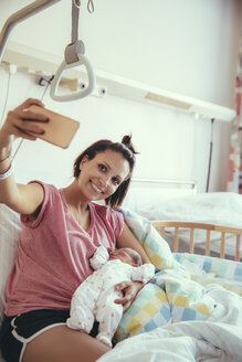 Mother taking a selfie with her newborn baby in hospital bed - MFF03981