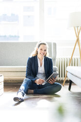 Smiling businesswoman sitting on floor using tablet - JOSF01746