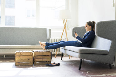 Businesswoman sitting on couch using cell phone - JOSF01752