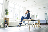 Businesswoman sitting on table in a loft - JOSF01758