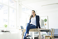 Portrait of smiling businesswoman sitting on table in a loft - JOSF01773