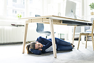Businesswoman lying under the table in office sleeping - JOSF01776