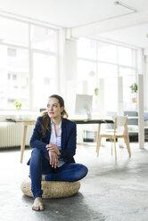 Businesswoman sitting on cushion on the floor - JOSF01779