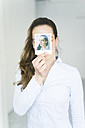 Woman covering her face with instant photo of herself - JOSF01788