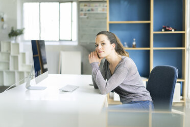 Portrait of woman sitting at desk - JOSF01791