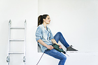 Woman sitting in a niche at ladder holding electric drill - JOSF01800