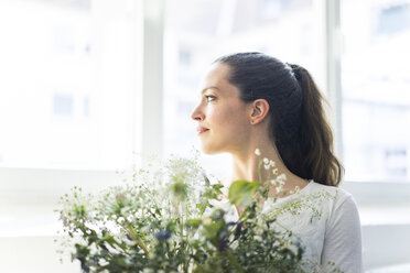 Woman with flowers looking out of window - JOSF01803