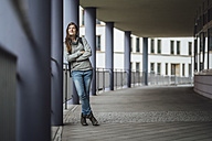 Smiling young woman leaning against column looking at distance - JSCF00001