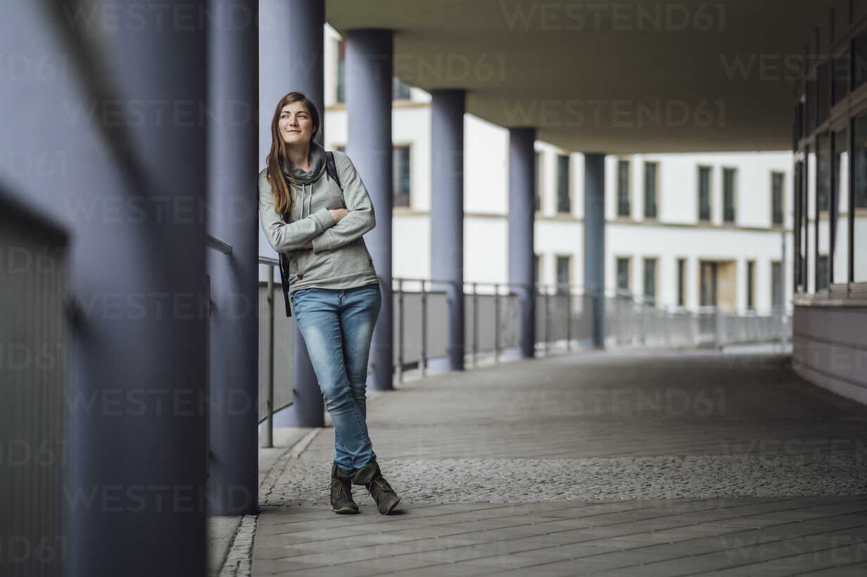 Smiling young woman leaning against column looking at distance - JSCF00001 - Jonathan Schöps/Westend61