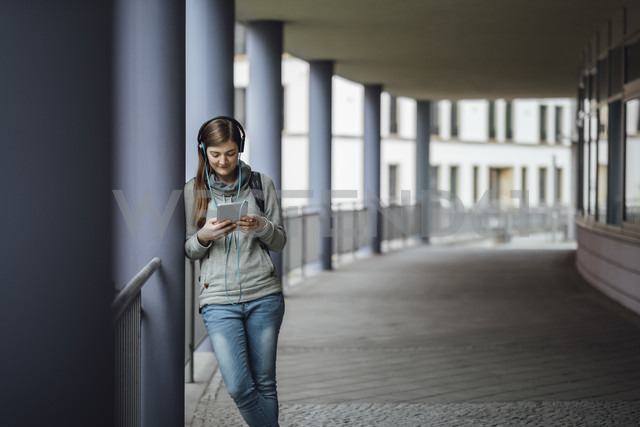 Young woman with headphones looking at mini tablet outdoors - JSCF00004 - Jonathan Schöps/Westend61