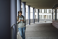 Young woman with headphones looking at mini tablet outdoors - JSCF00004