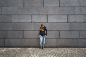 Young woman standing in front of grey facade looking up - JSCF00007