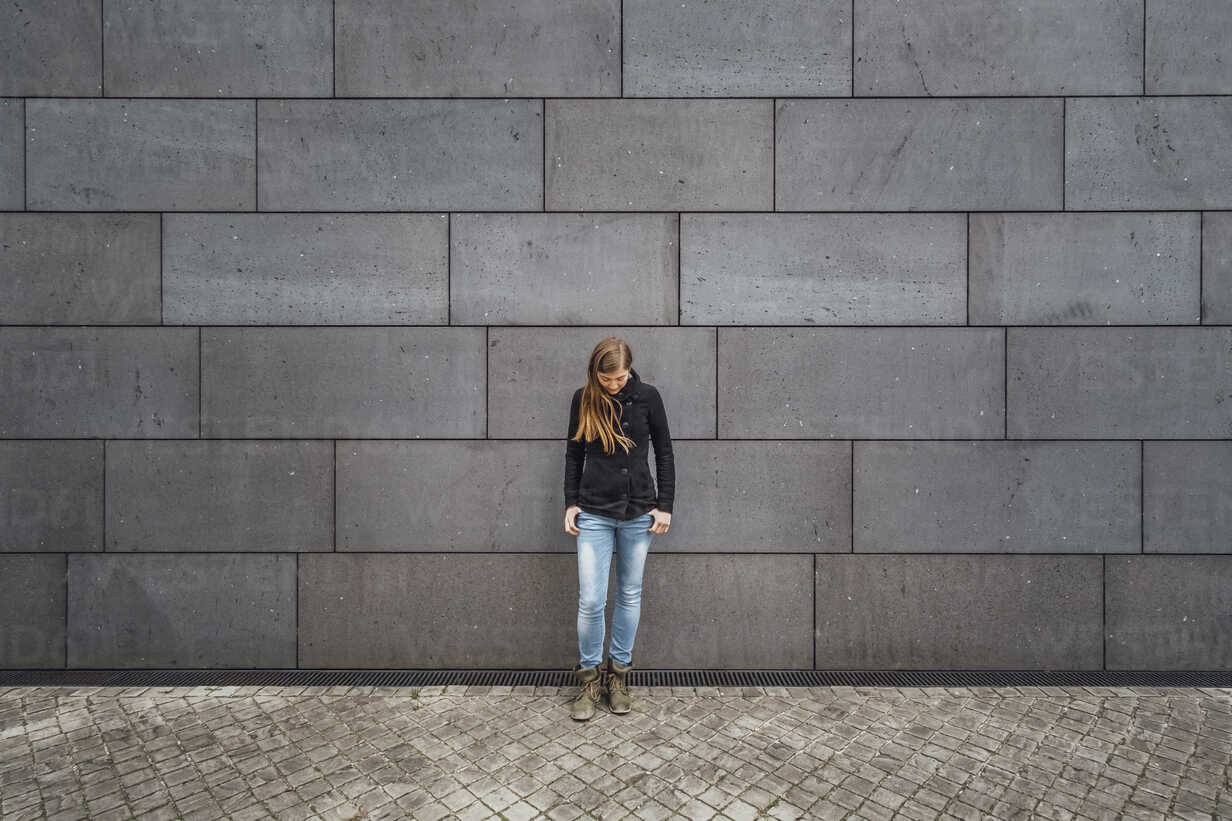 Young woman standing in front of grey facade looking up - JSCF00007 - Jonathan Schöps/Westend61