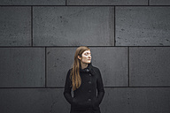 Young woman with eyes closed standing in front of grey facade - JSCF00010