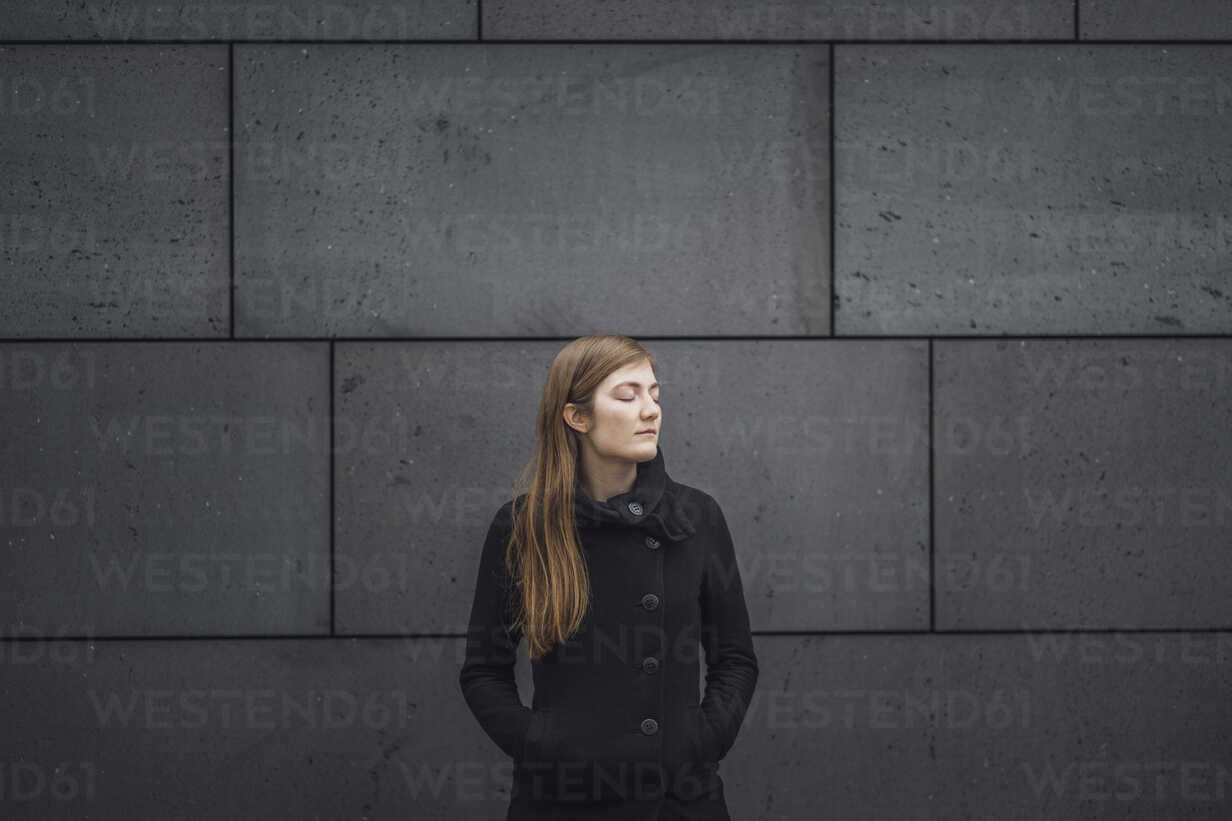 Young woman with eyes closed standing in front of grey facade - JSCF00010 - Jonathan Schöps/Westend61