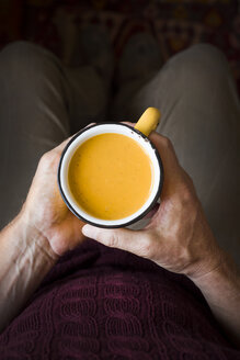 Man's hands holding enamel cup of pumpkin soup - CZF00310