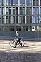 Mature businessman pushing bicycle in the city - FKF02518