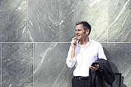 Mature businessman with earphones and smartphone at a wall - FKF02521