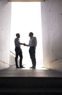 Two businessmen shaking hands in a passageway - FKF02530