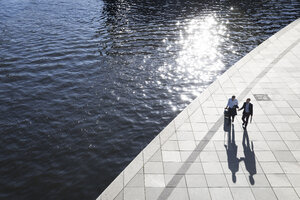 Two businessmen walking and talking at the riverbank - FKF02536
