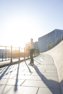 Businessman riding skateboard in the city - FKF02542