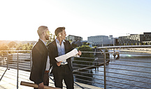 Two architects with blueprint standing on a bridge in the city - FKF02545