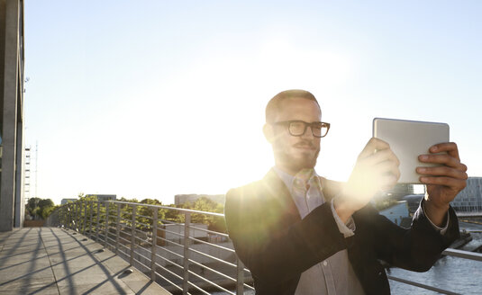 Businessman taking a selfie with tablet on a bridge in the city - FKF02548