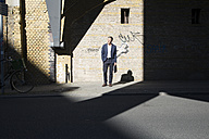 Businessman standing at graffiti wall looking around - FKF02569