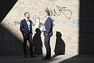 Two businessmen talking at graffiti wall - FKF02572