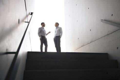 Two businessmen talking in a passageway - FKF02578