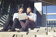 Two smiling businessmen sitting on stairs using laptop - FKF02587
