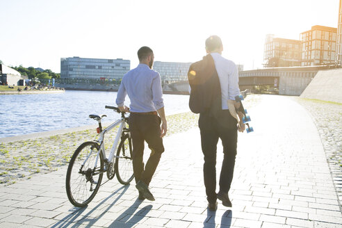 Two businessmen walking with bicycle and skateboard at the riverbank - FKF02590