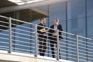 Two businessmen talking on a bridge in the city - FKF02593