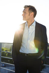 Confident mature businessman on a bridge in backlight - FKF02599