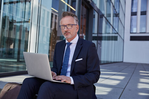 Portrait of businessman using laptop outdoors - SUF00286