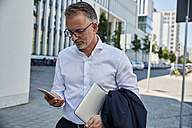 Businessman with laptop looking at cell phone - SUF00298