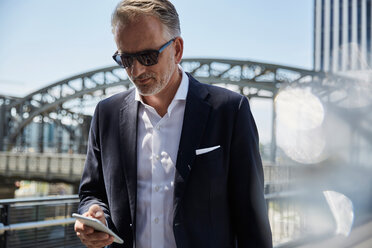 Germany, Munich, portrait of businessman wearing sunglasses looking at cell phone - SUF00301
