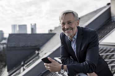 Grey-haired businessman on balcony holding smartphone smiling into camera - SBOF00732