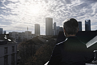 Grey-haired businessman on balcony looking over city - SBOF00735