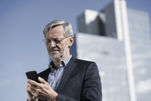 Grey-haired businessman typing into smartphone - SBOF00738