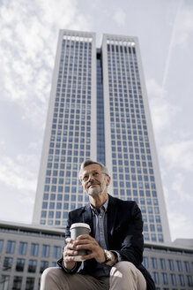 Grey-haired businessman in front of skyscraper holding coffee to go - SBOF00744