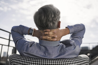 Grey-haired businessman relaxing in chair on balcony - SBOF00747