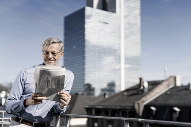 Grey-haired man on balcony reading newspaper - SBOF00753