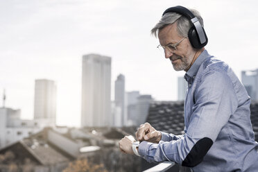 Grey-haired businessman with headphones looking on smartwatch - SBOF00759