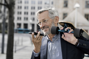 Grey-haired businessman with longboard and smartphone - SBOF00762