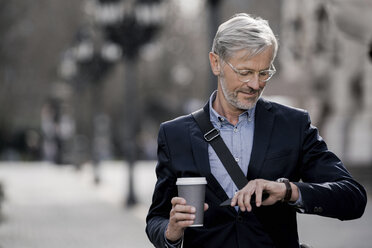 Grey-haired businessman in the city looking at watch holding coffee to go - SBOF00765