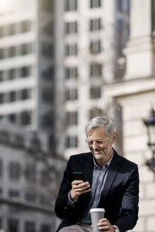 Grey-haired businessman in the city with smartphone and coffee to go - SBOF00768