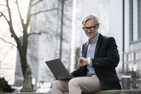 Grey-haired businessman working with laptop on wall in city looking at his smartwatch - SBOF00771