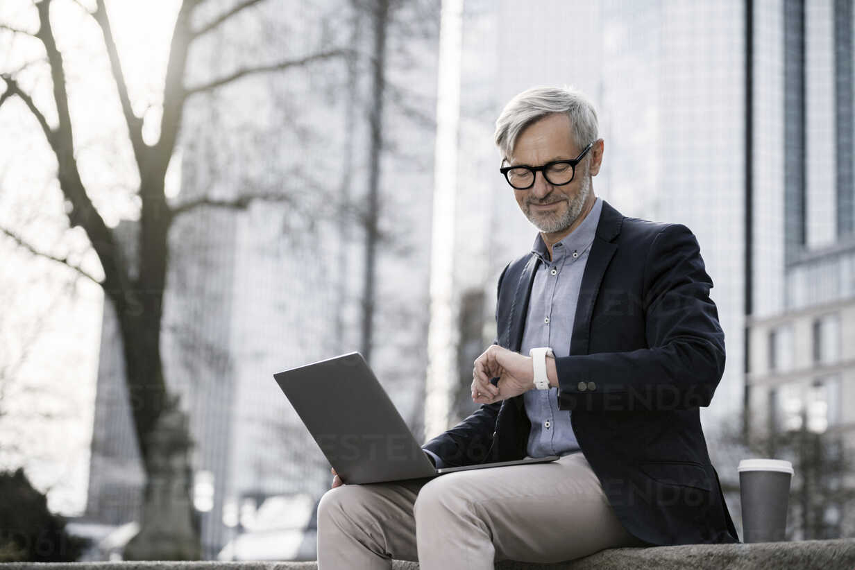 Grey-haired businessman working with laptop on wall in city looking at his smartwatch - SBOF00771 - Steve Brookland/Westend61