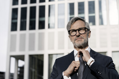 Grey-haired businessman adjusting his tie in front of skyscraper - SBOF00774